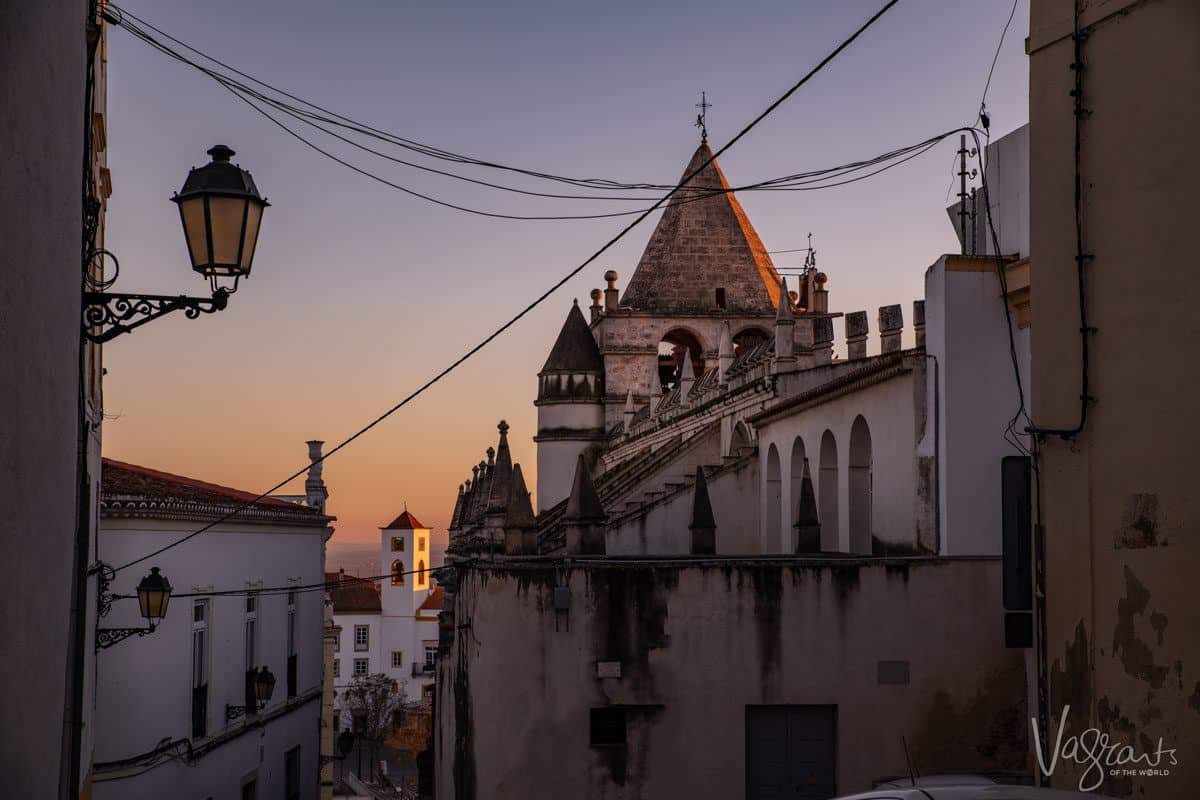 the sun setting over the spires of the church in elvas.
