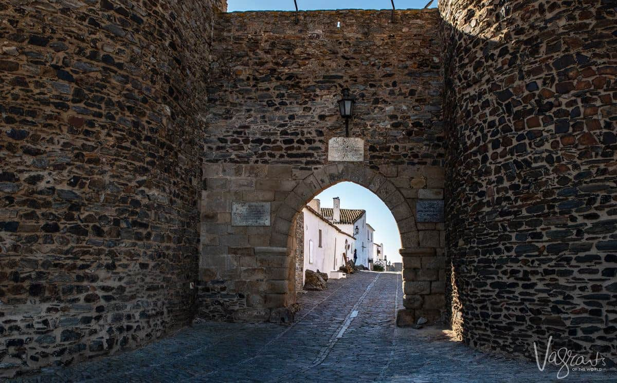 archway entrance of Monsaraz castle with cobblestone street leading into the town.  A visit to Monsaraz is one of the best things to do in alentejo portugal