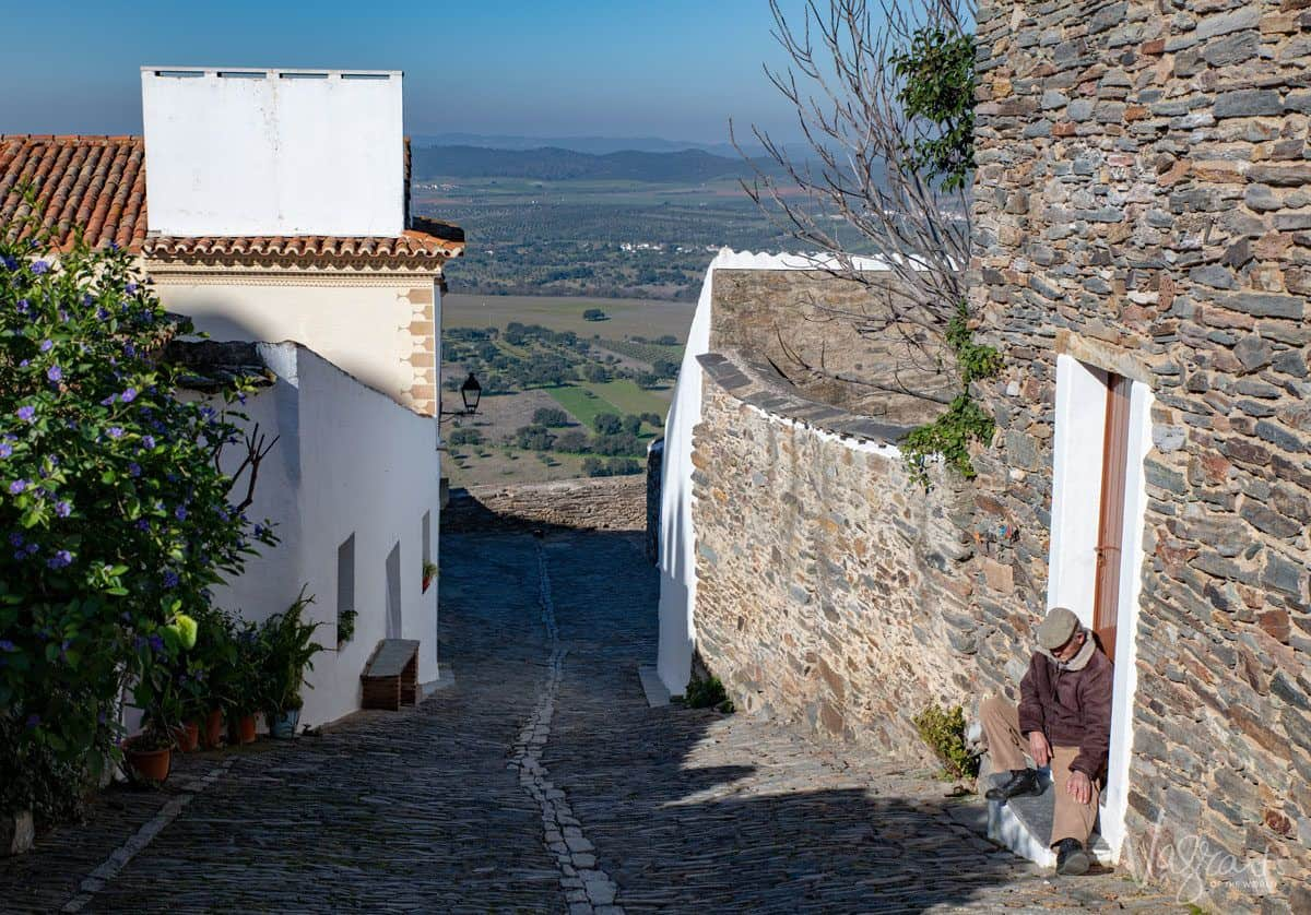 man sitting on step of cobblestone street in Monsaraz.  Monsaraz wine is a very highly rated alentejo wine