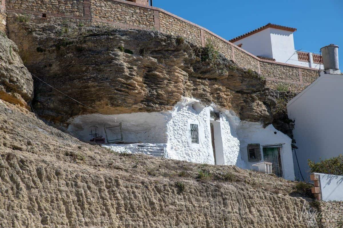 Small unique white house built into the rock cliff in Setenil de las Bodegas.