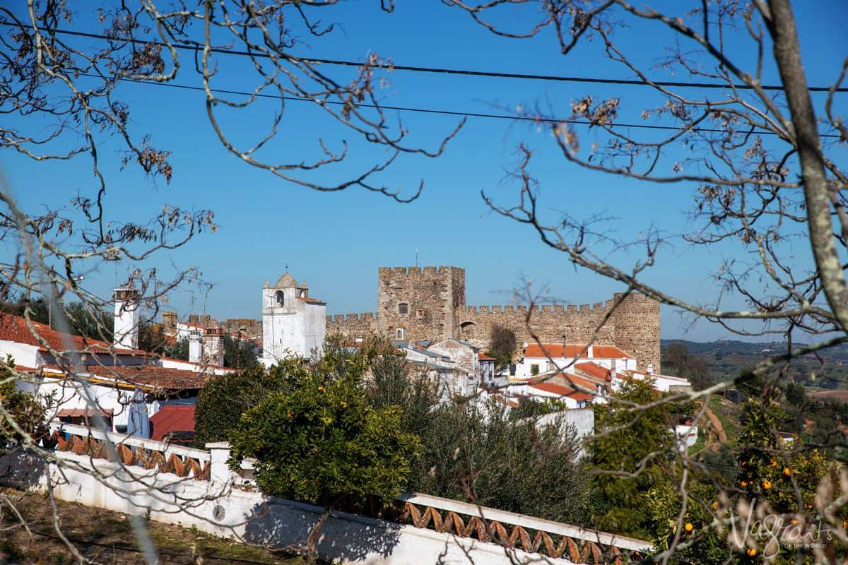 a view across white village to the castle of terena.  add this to your alentejo portugal itinerary.