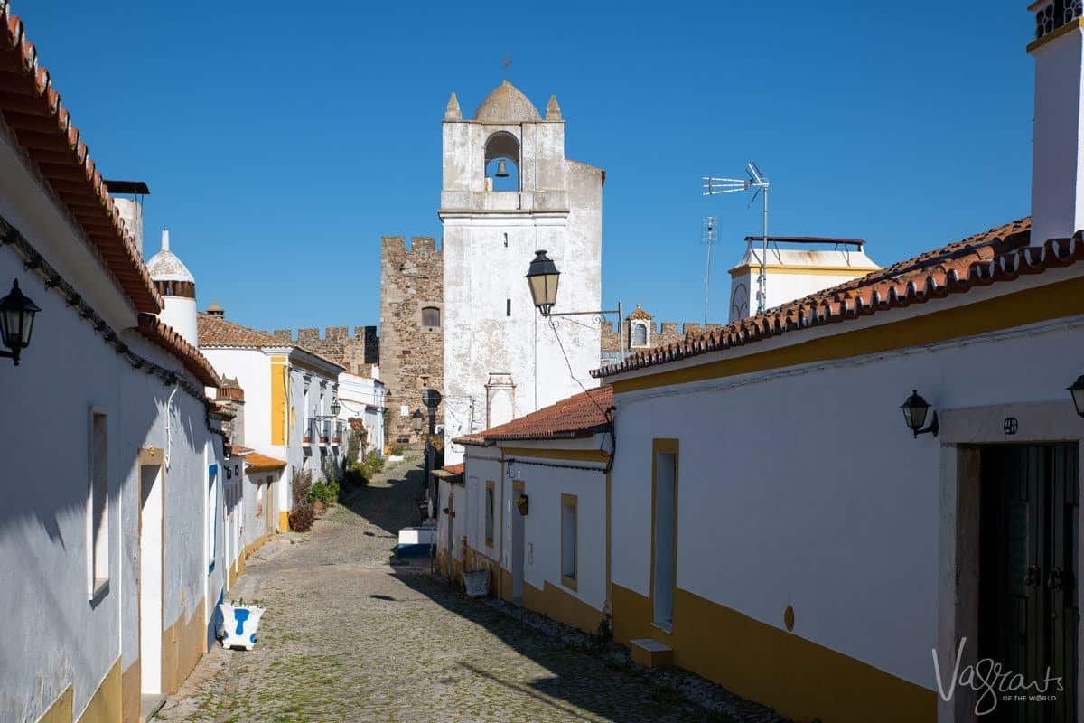 white and yellow walls of houses leading up to the terena castle.  we stopped here on our alentejo road trip and it was one of the best things we did.
