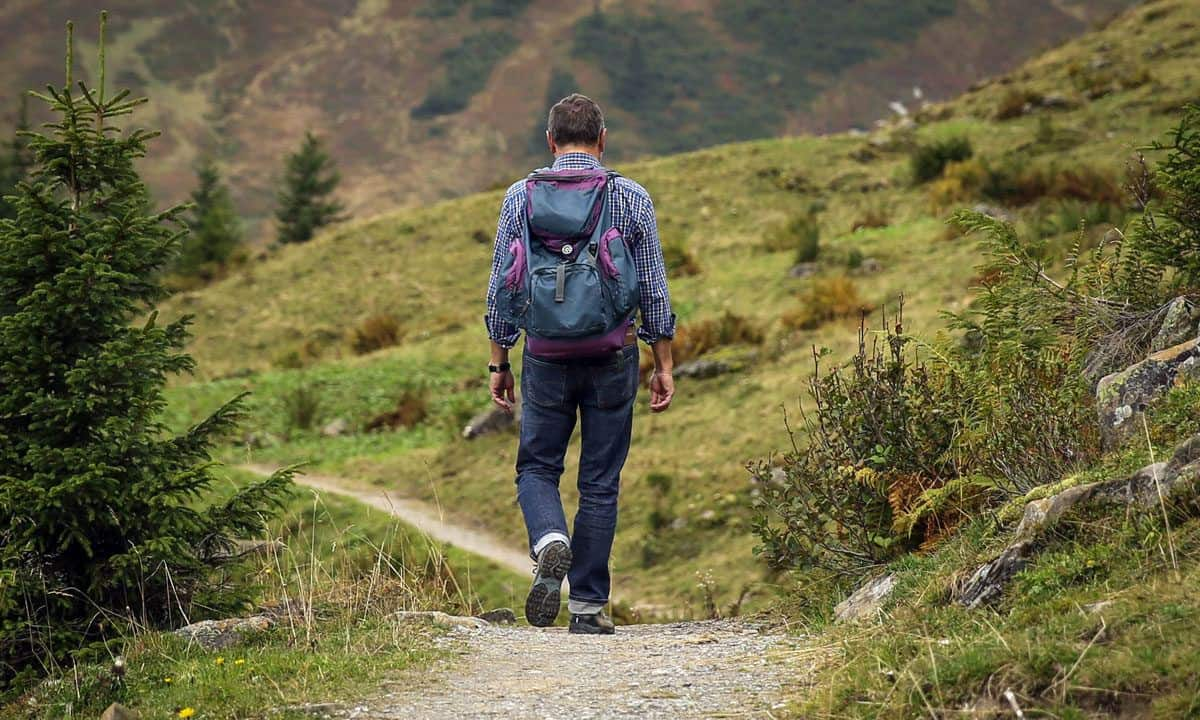 man with backpack walking along a country path on his self guided walking holiday UK