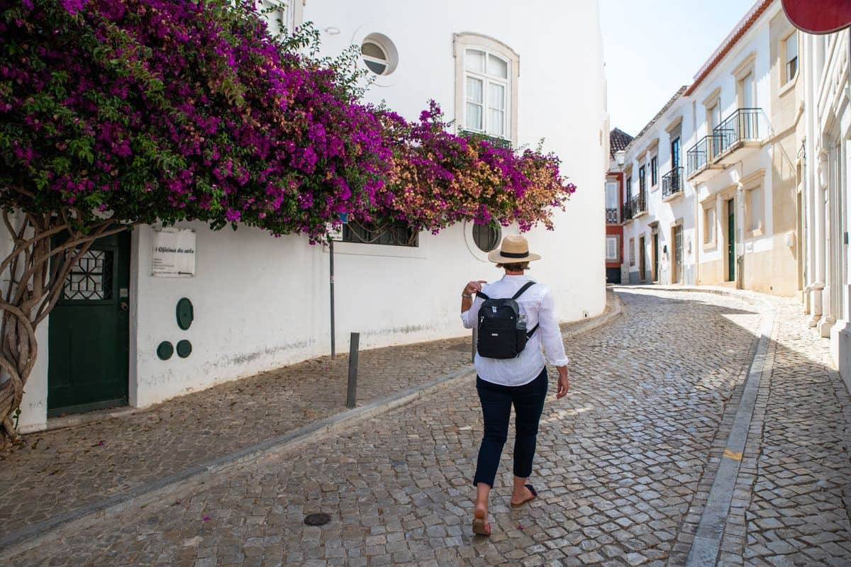 women walking under pink flowers wearing a black travel back pack. if you are looking for the perfect backpack for travel then this womens range may be for you