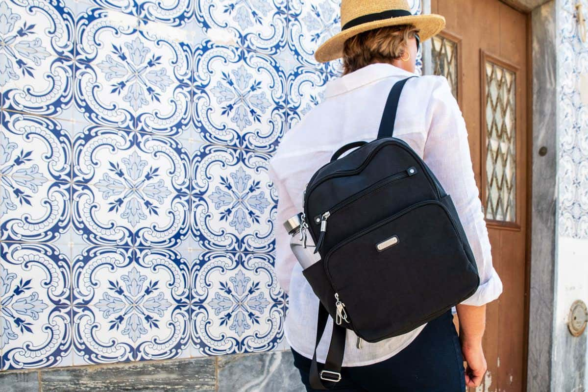 black womens travel backpack slung over the shoulder and set against a blue and white tiled wall. the may be a womens best travel backpack