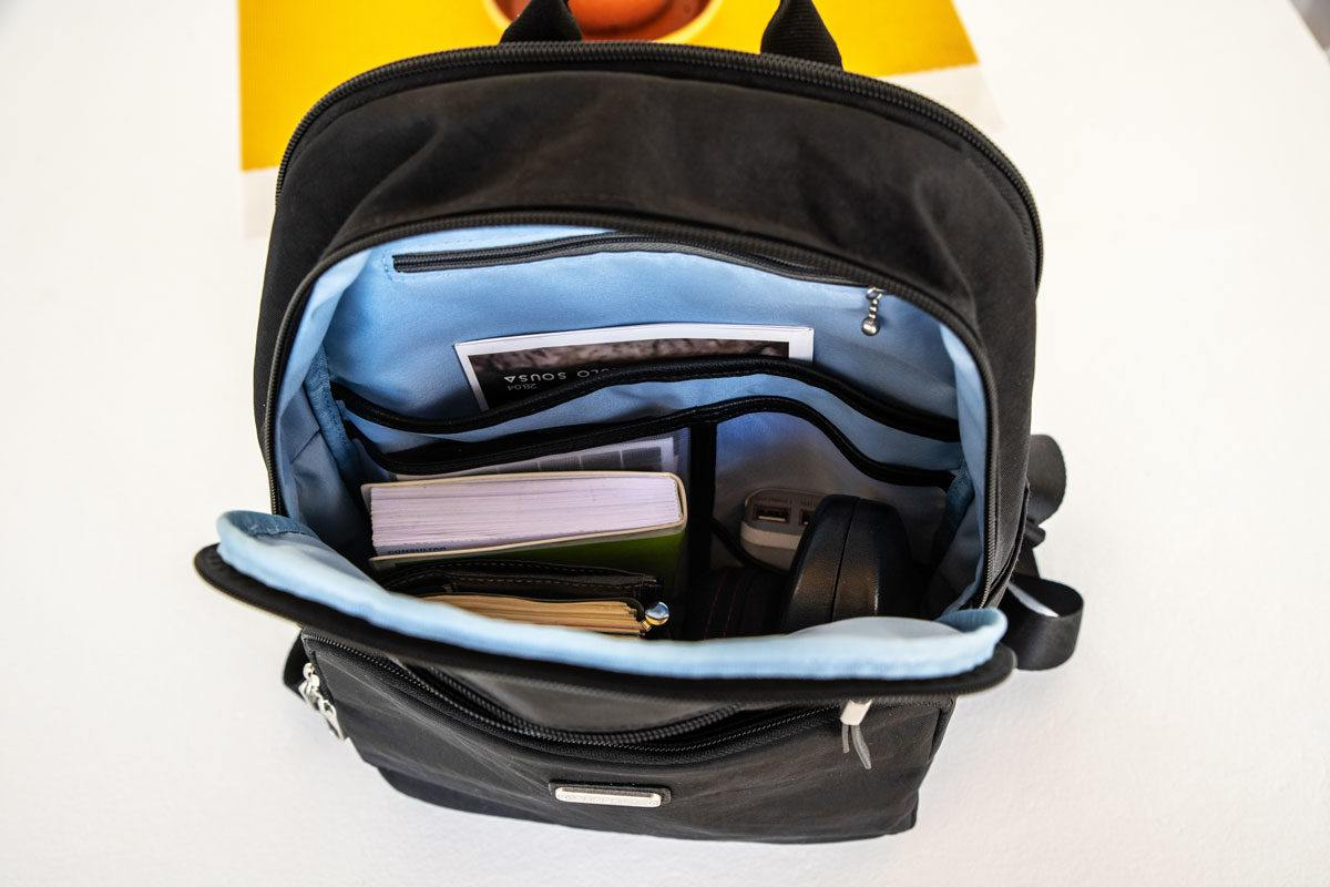 looking inside a back pack full of books and other travel items.