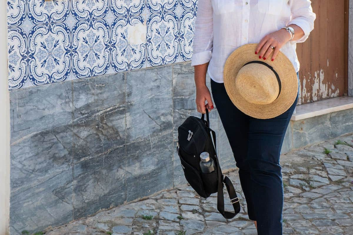 women holding a hat and backpack. this versatile womens travel backpack can be carried by the handle when not being worn on the back