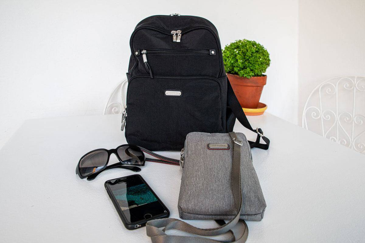 a black cross body bag ad grey travel purse next to sunnies and a phone.  the best travel purses need to have all the features you will find in this article.  that is why baggallini make the perfect womens travel purse