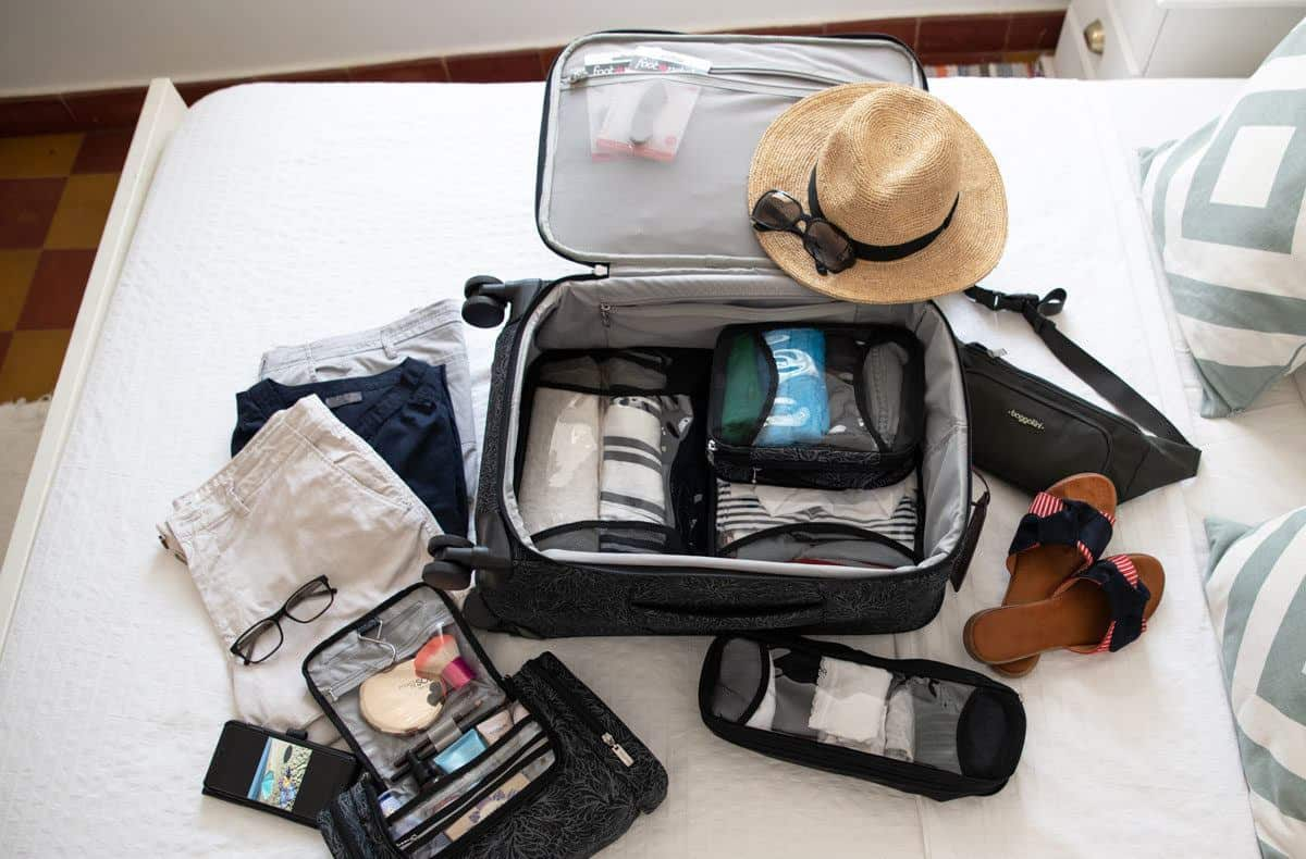 an open bag showing clothing items laid out for the next big vacation.  this little light weight four wheeled travel bag may be the ultimate choice for carryon