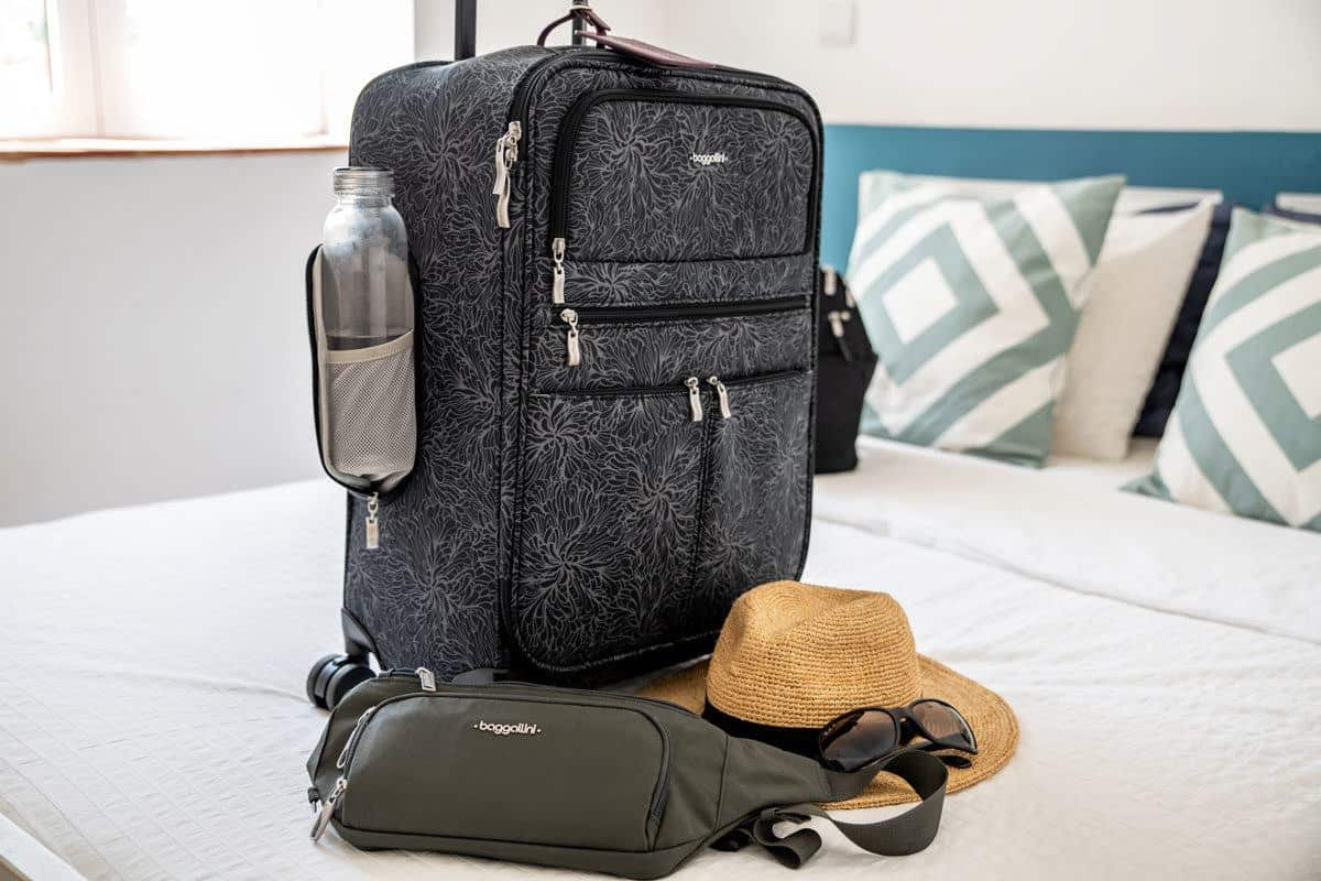 grey baggallini travel bag on a bed with a bum bag and hat.  if you are looking for the  best luggage for travel then you cant beat these travel bags for women
