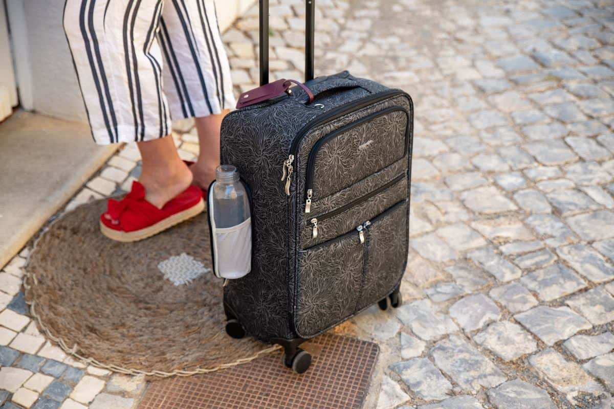 women wearing red shoes with the best carryon travel bag for women on the cobblestones outside her hotel