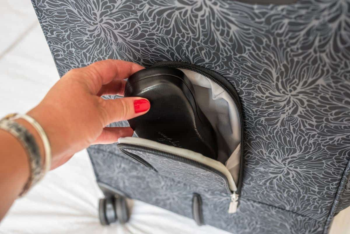 hand placing glasses case into secret compartment built into the back of a carryon travel bag.  security and antitheft qualities of travel bags is very important when choosing the best travel bag