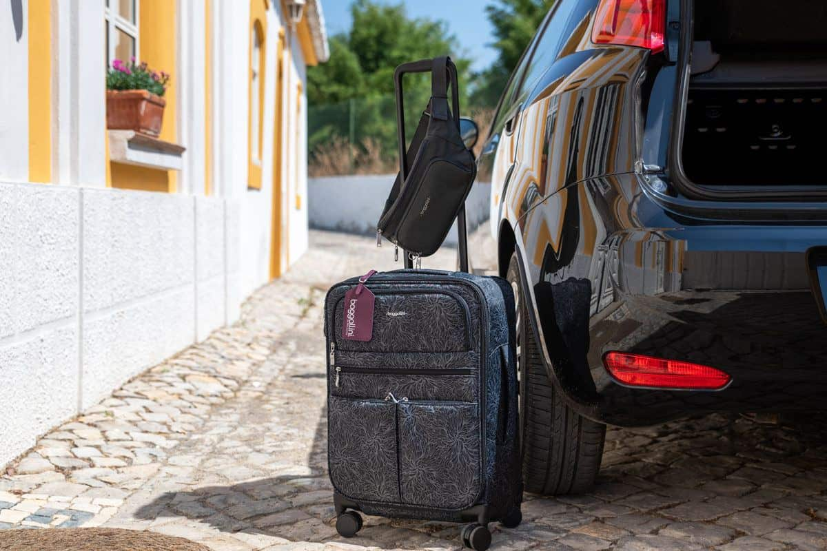 a baggallini carryon travel bag and bum bag sitting next to the open boot of a car.  these bags are the best travel bags for women