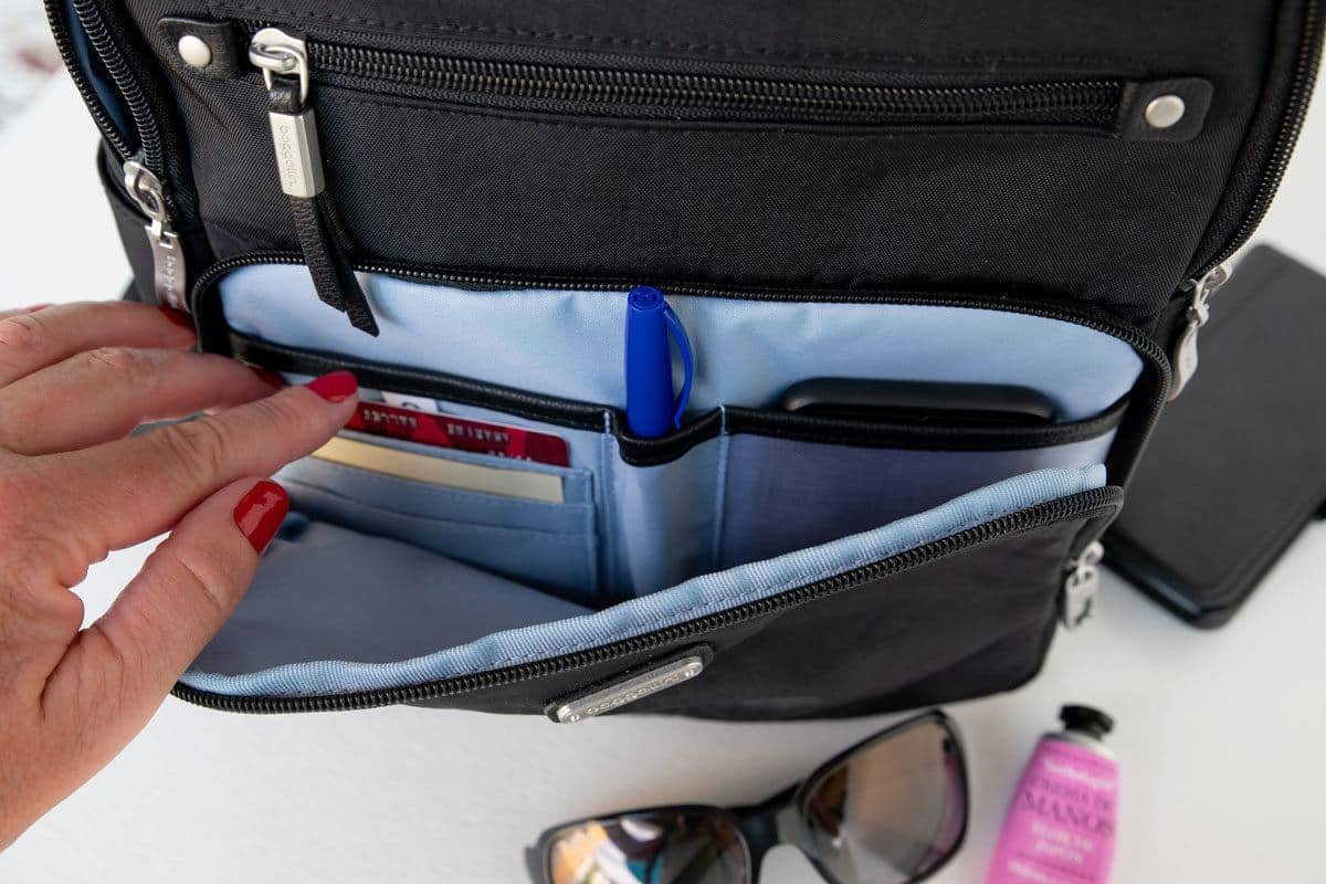 the rfid section of the antitheft area of a black backpack showing credit cards and a pen.  a good antitheft back pack for travel is essential