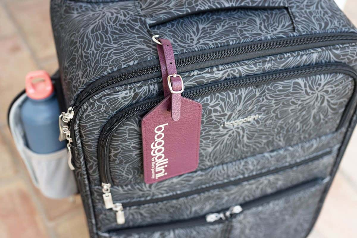 grey carryon bag with red leather luggage tag.  these stylish and practical travel bags are the best travel bags for women.