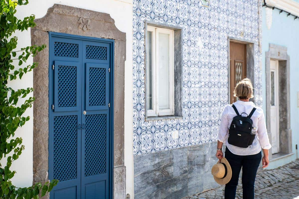 girl with black backpack outside a tiled walled house in Lisbon.  this style of backpack is a perfect womens travel backpack