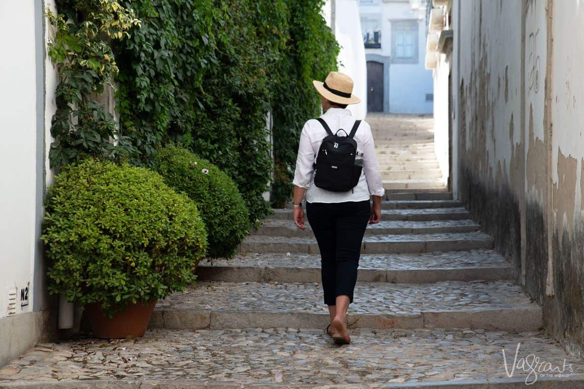 women walking along cobblestone street wearing black womens travel backpack.  combine this with baggallini's purses for travel and you have the perfect combo