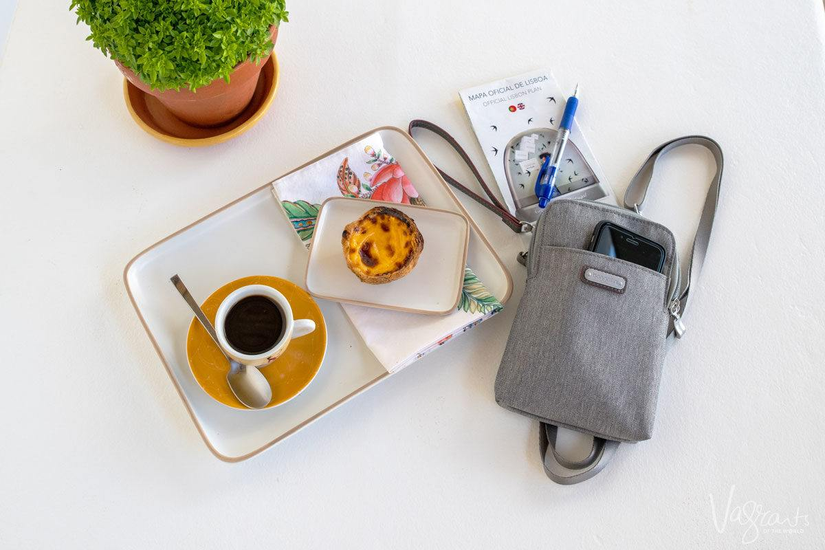 a womens cross body travel bag on a table next to a cup of coffee and a pastel de nata. this may be the best travel purse for you
