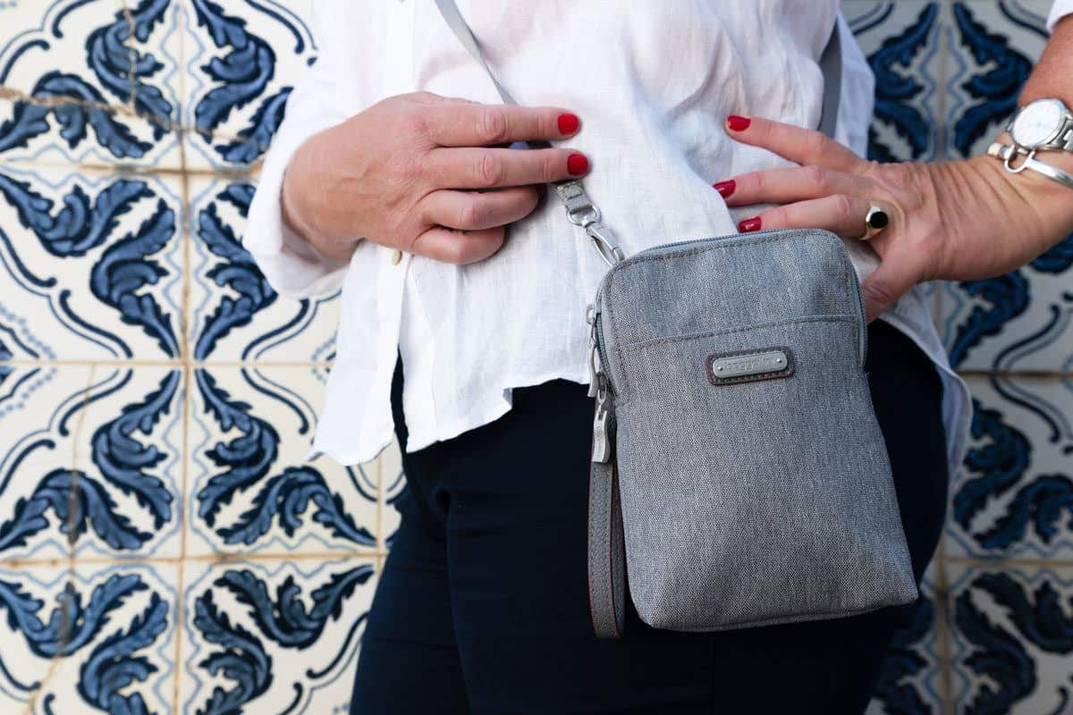 side view of a women wearing a grey cross body purse. it is not easy to find the best purses for travel but baggallini seem to be doing a good job of producing what a women wants in a travel purse