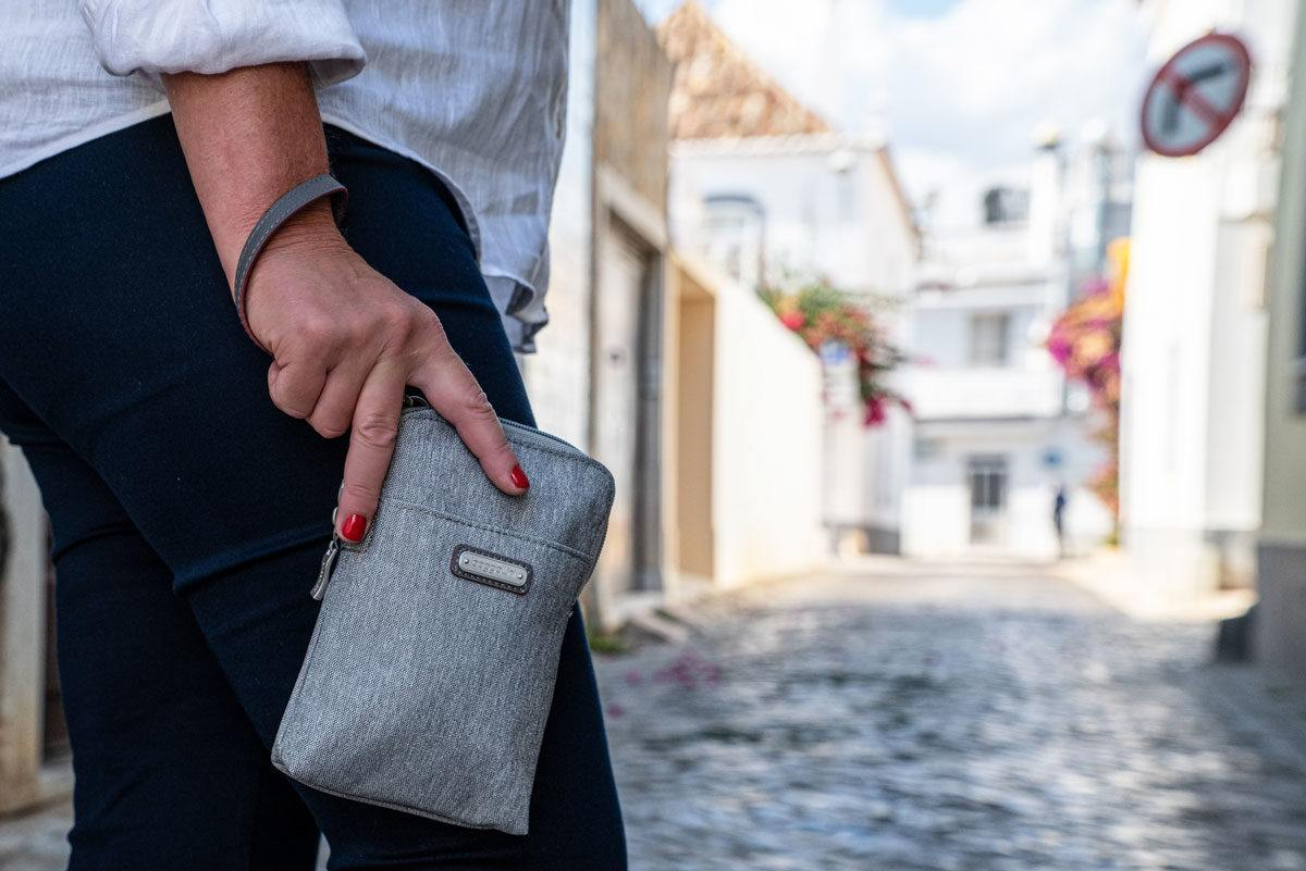 women holding a grey travel purse with wrist loop. these travel purses are best sellers