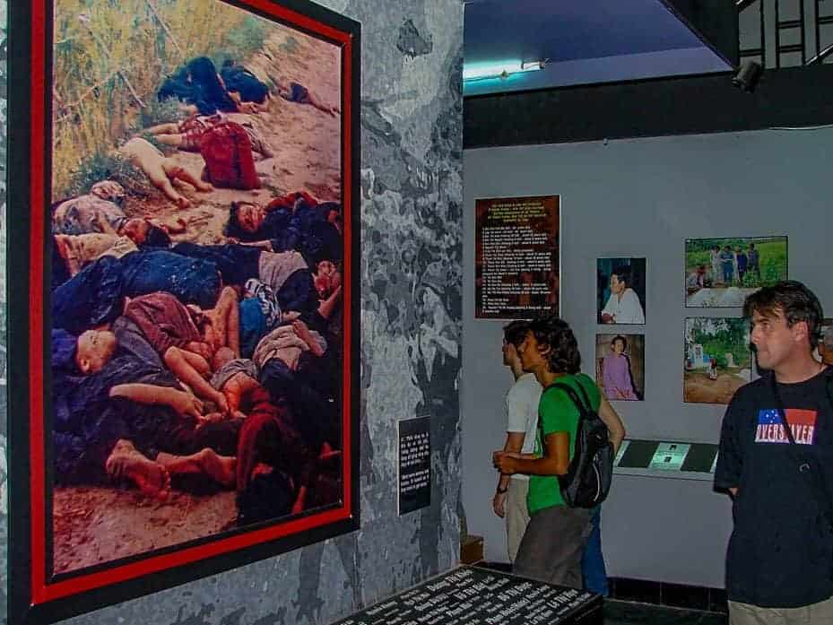 tourist looking at a photograph of dead vietnamese at the war remnants museum. this is the most popular and interesting things to do in Ho Chi Minh city