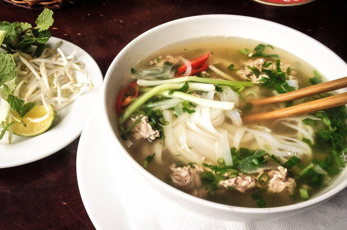 Bowl of pho with noodles, chop sticks and chicken. best street food in ho chi minh city.