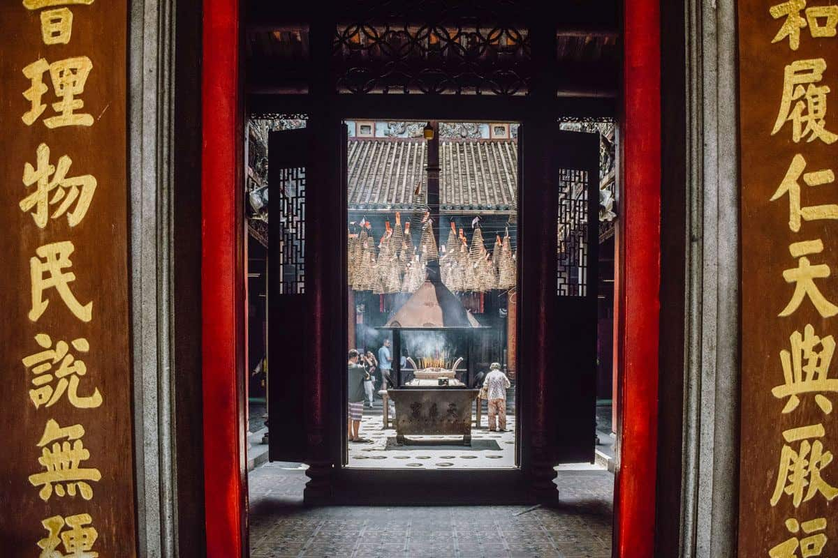An incense fire as seen though the arched entrance. Add a stop here to your Ho chi minh city itinerary.