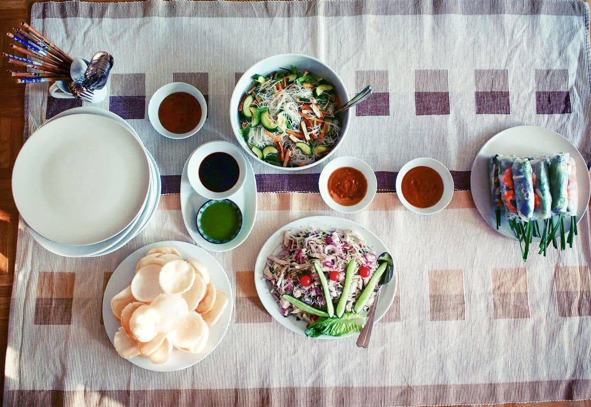 table laid out with vietnamese food and dipping sauces. the best food in ho chi minh city may well be what you buy at the markets and cook at home.