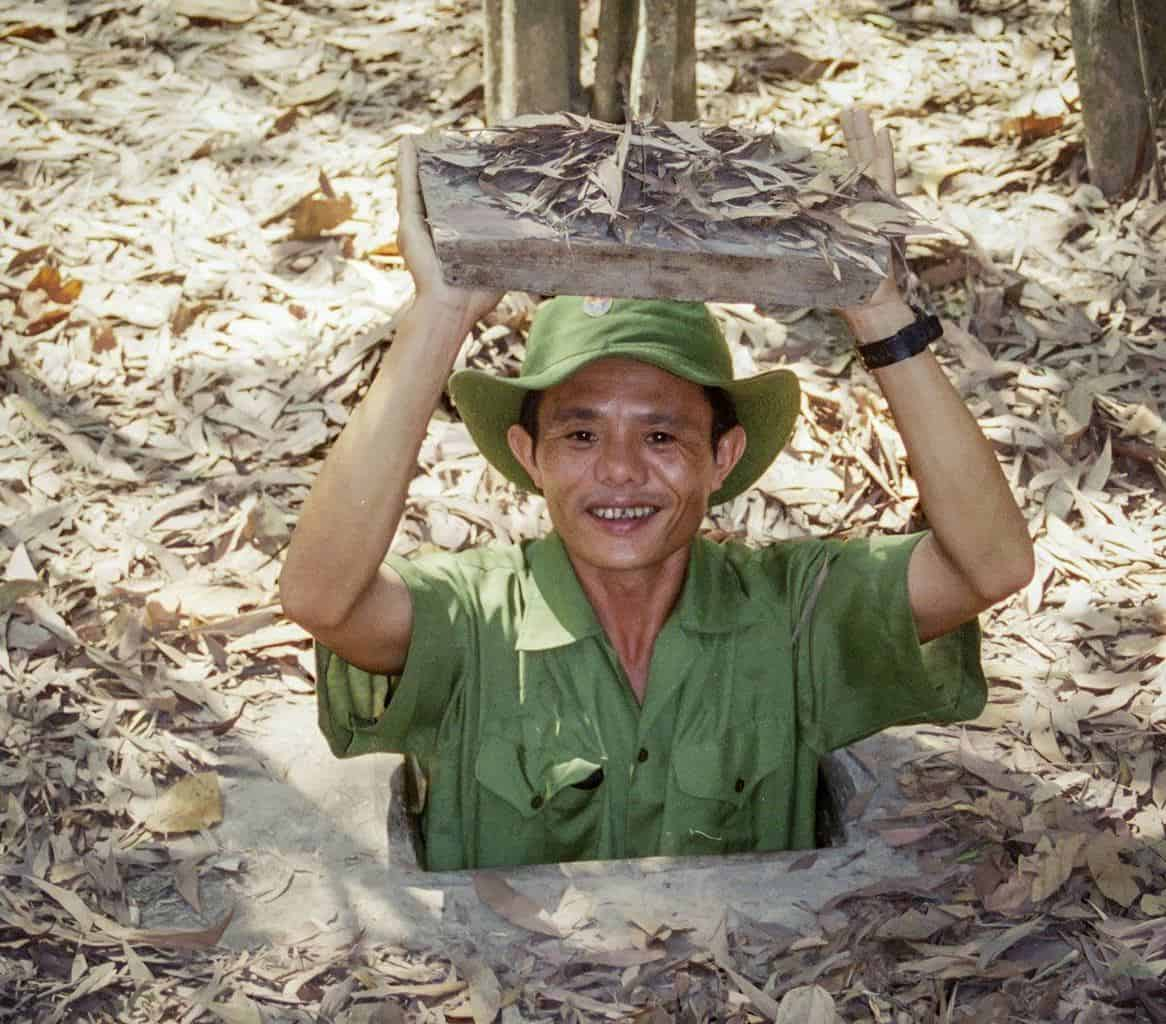 vietnamese man holding lid of tunnel at cu chi tunnels. the best day trip from ho chi minh city