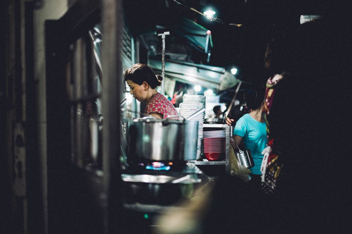 women cooking with pot on the stove in the foreground. The ben thanh markets are a interesting thing to see in Ho Chi Minh city at night.