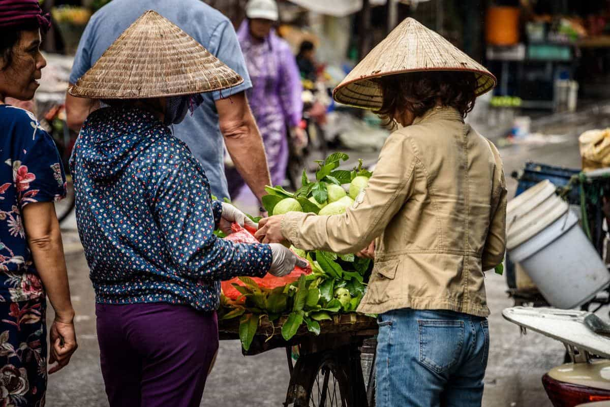 two street vendors wearing conical hats selling vegetables. shopping at the street vendors is a fun thing to do in Ho Chi Minh city