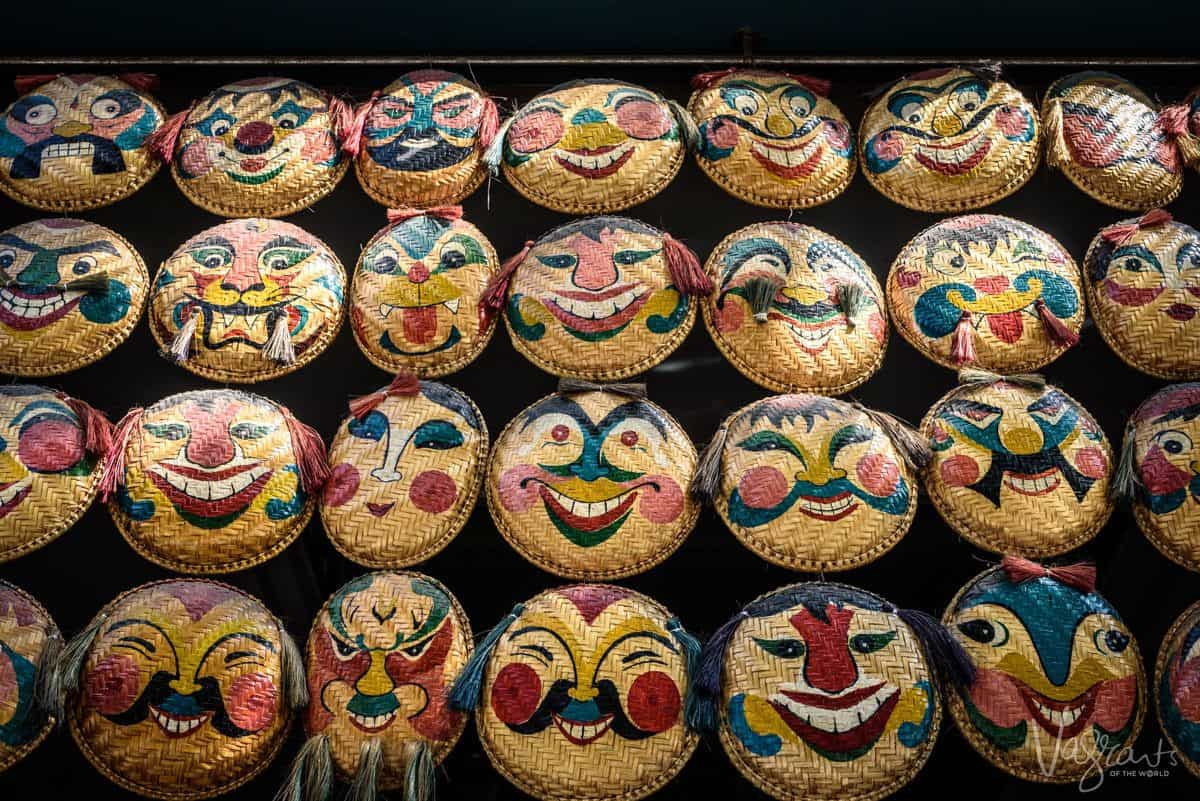 creepy faces painted on woven plates, an unusual souvenir to buy in ho chi minh city