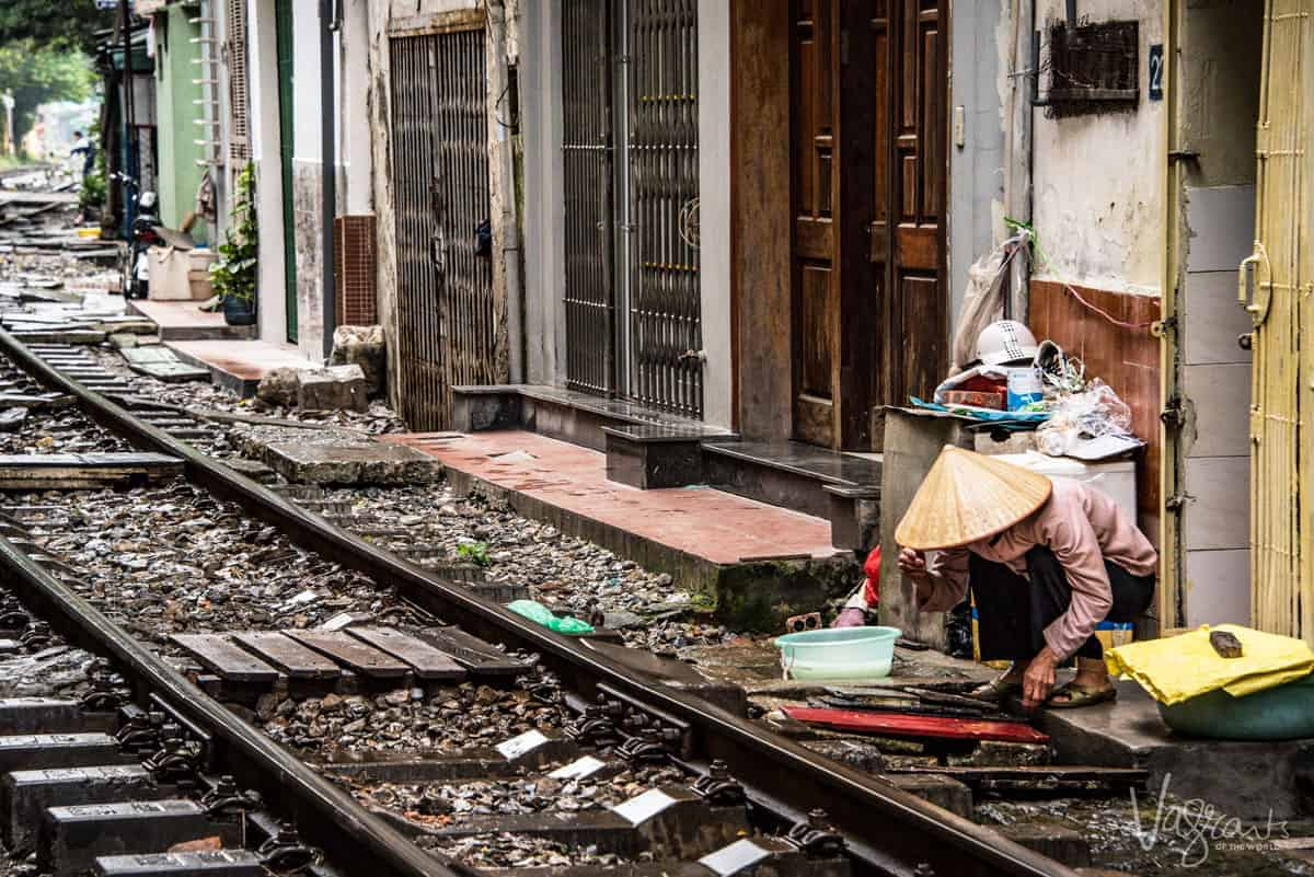 Lady washing dishes next to the train tracks in train street.
