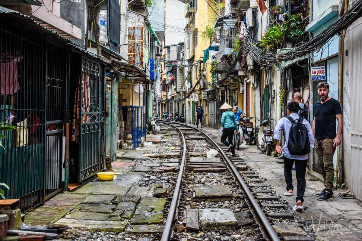 People walking next to the tracks on train street, one of the most popular things to see and do in Hanoi Vietnam.