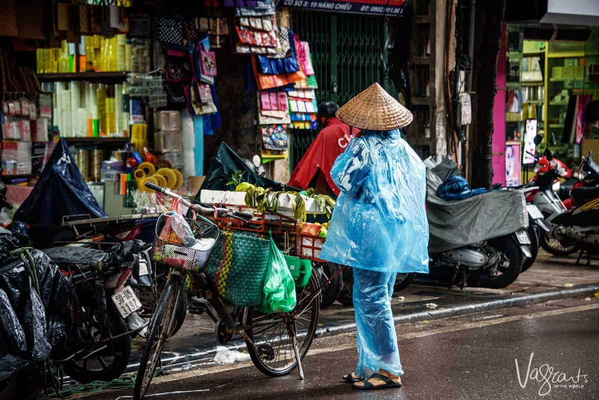 Lady in 2 piece blue rain coat with conical hat next to her bicycle. Watching the locals get around is one of the best free things to do in Hanoi Vietnam.