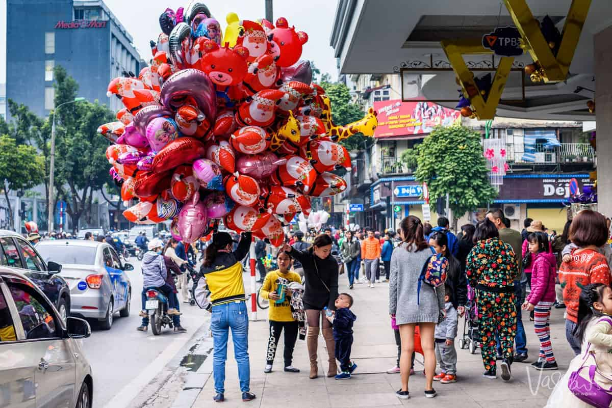 A women holding hundreds of colourful helium balloons on the street.