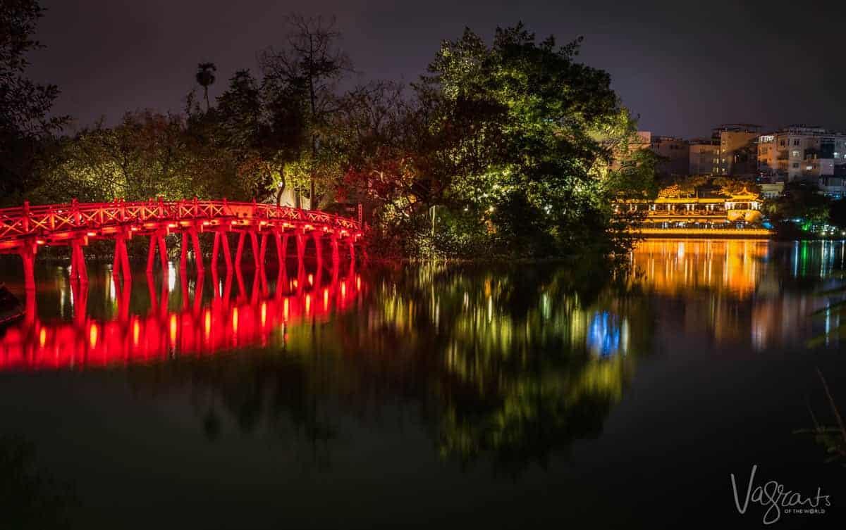 Bridge lit red crossing turtle lake in Hanoi Old Quarter.
