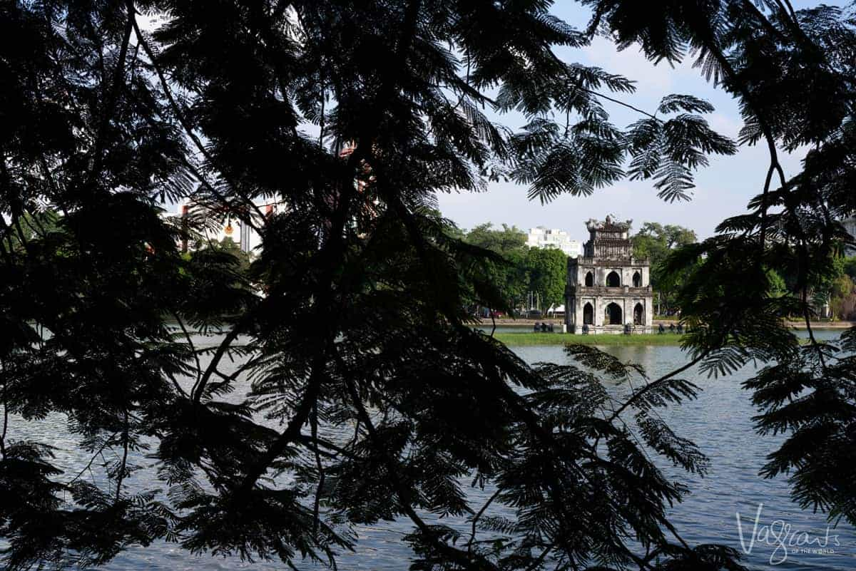 Temple framed by tree leaves in the middle of Turtle Lake Hanoi.