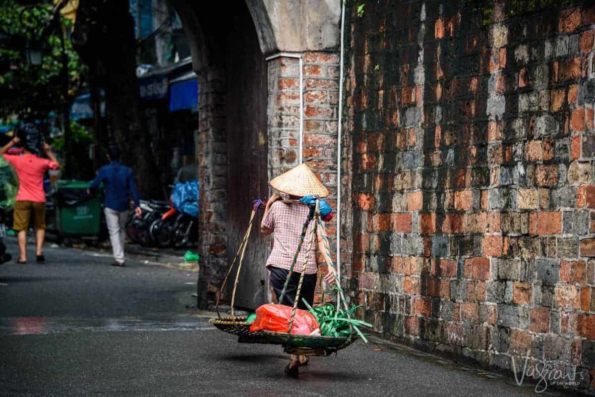 Women in conical hat carrying her vegetables to market. Shopping from these ladies in Hanoi Old Quarter is a great thing to do in Hanoi.