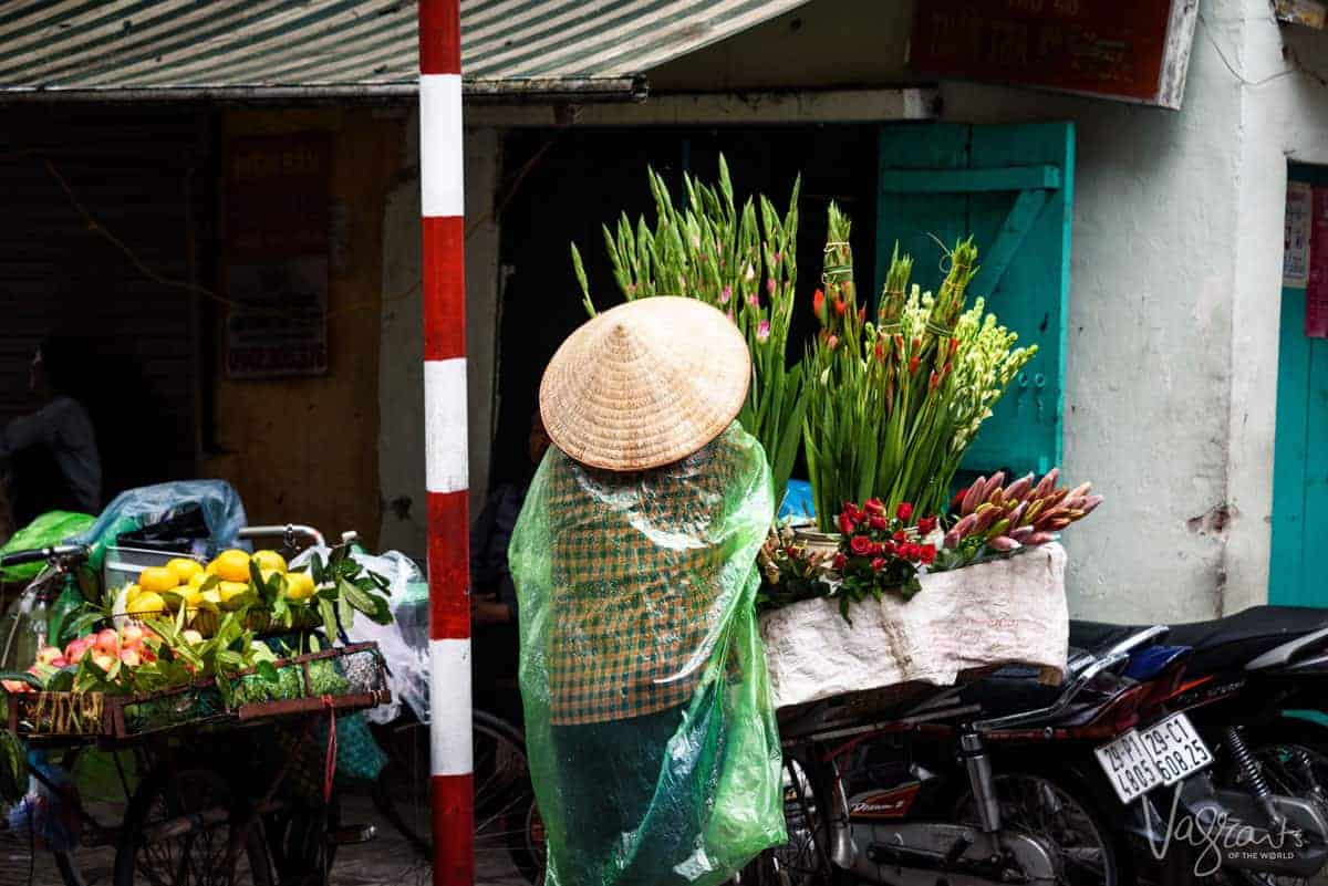 Flower seller and her baskets of flowers on motorbike outside the best place for shopping in Hanoi, the Dong Xuan Market.