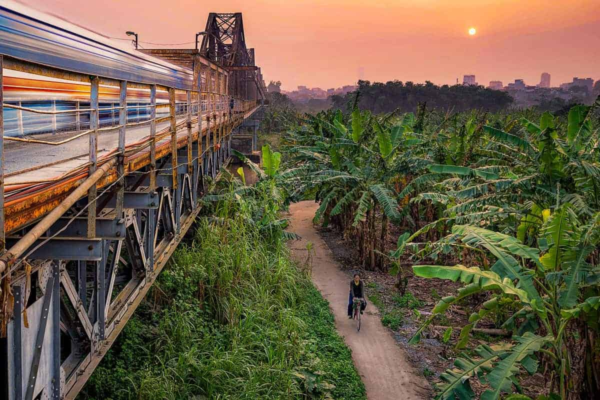 Day trip from Hanoi is to Long Bien Bridge for sunrise and to see people cycling through the plantations beside the bridge.