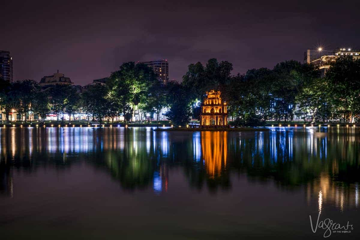 Turtle tower lit with golden light, spending time around this lake is the best thing to do in Hanoi at night.