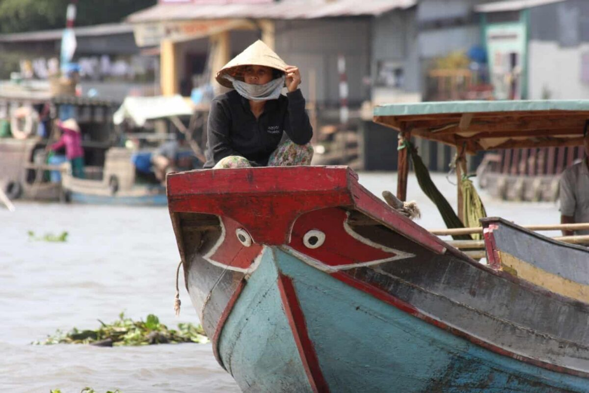 women in conical hat sitting on the bow of a junk on the mekong delta. The best day trips from ho chi minh city vietnam