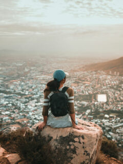 Female traveller wearing a backpack sitting on a rock at a lookout over a city and harbour.