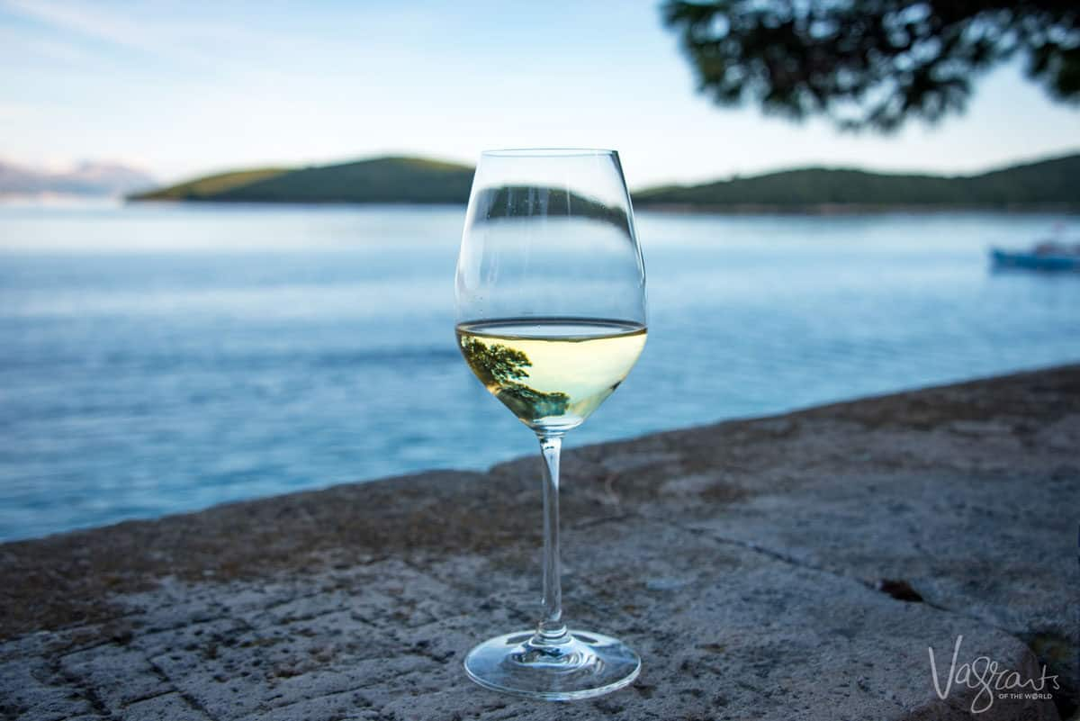 A glass of white wine on a ledge next to the ocean.