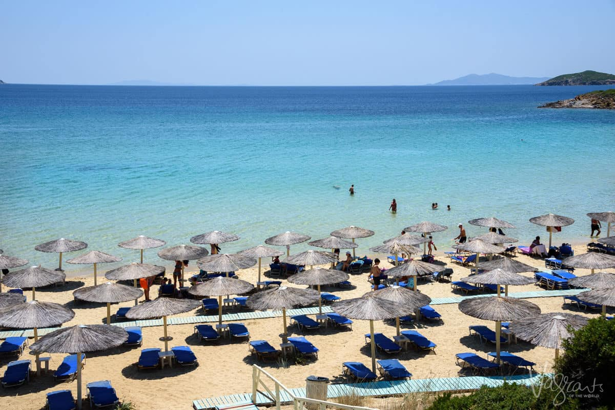 A beach full of sun beds and shades leading down to blue clear water, a perfect spot to spend summer in Europe.