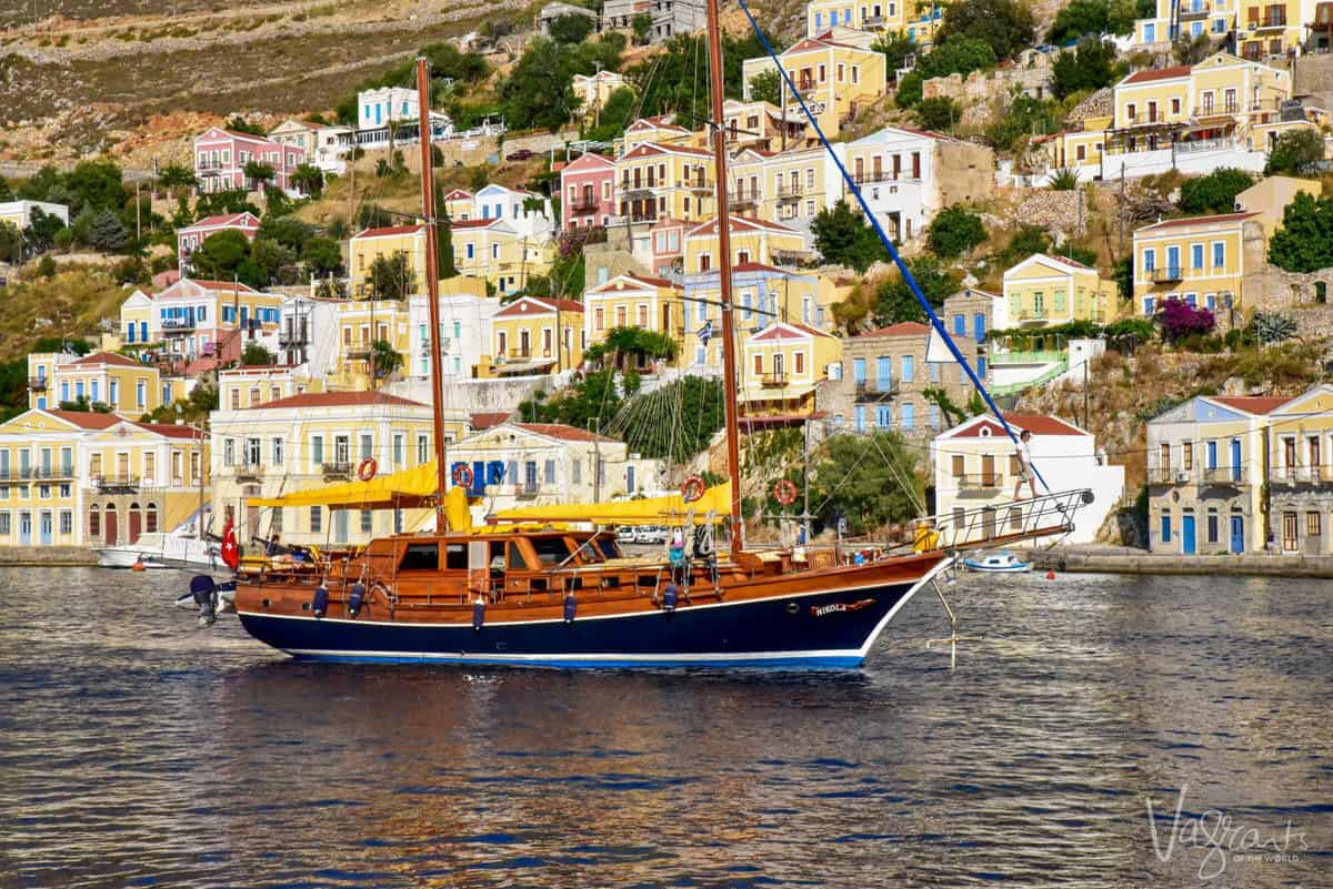 a motor yacht sailing past a hillside of old greek homes on Symi island. Spring on Symi is the best time to visit europe for honeymoon.