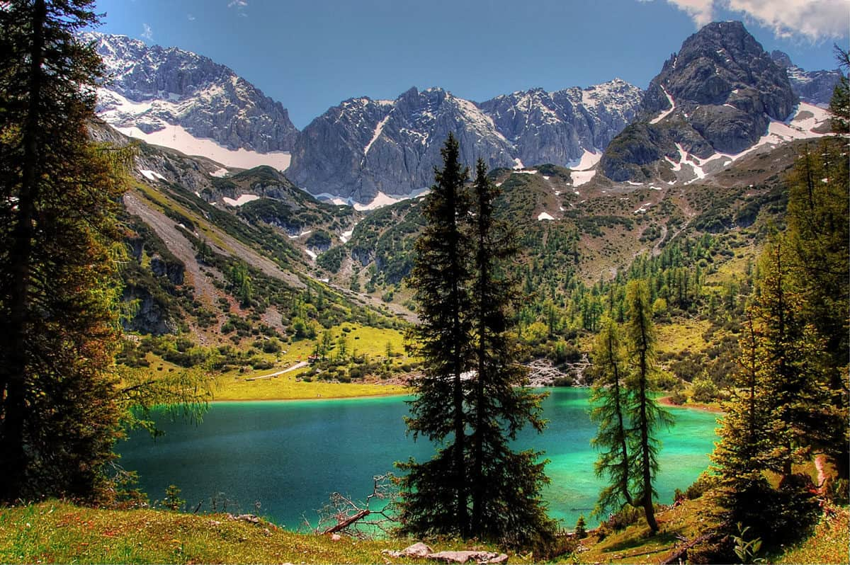 blue green lake surrounded by snow capped mountains, tirol berge Austria.