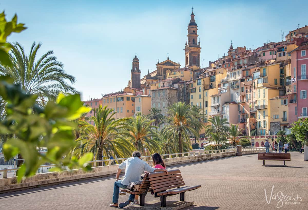 Couple sitting on a park bench with an old town in the background. The best time to visit Europe is when the weather is mild and the skies are clear, spring and autumn.