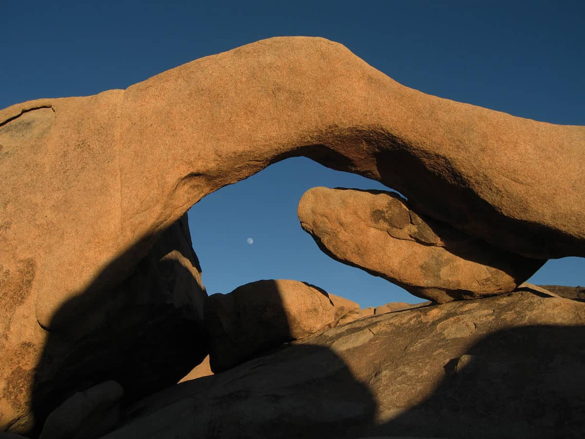 Arch Rock against a dark sky with moon. Arch Rock trail is one of the most popular hikes in Joshua Tree